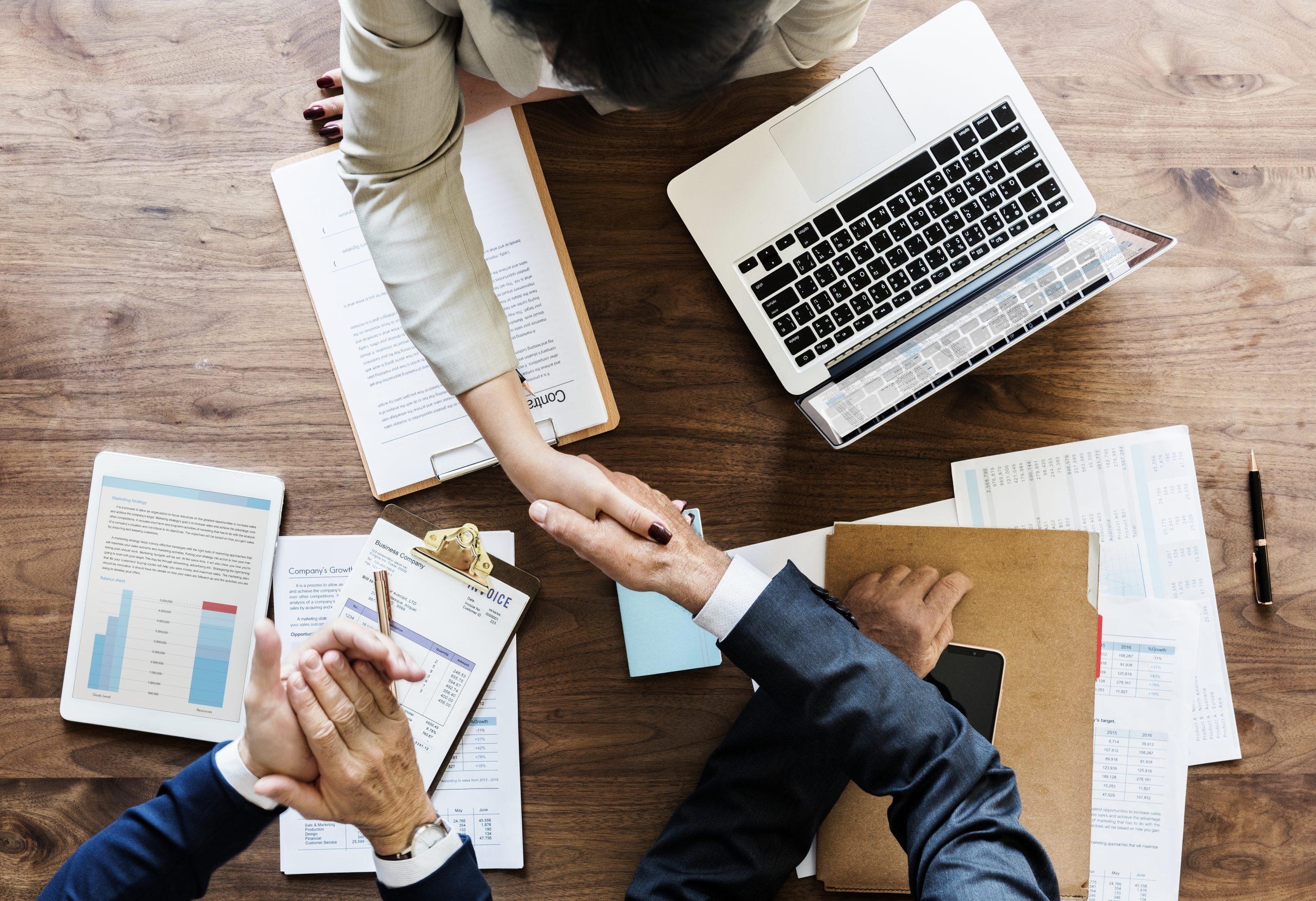 Dos personas estrechan las manos tras cerrar un acuerdo.