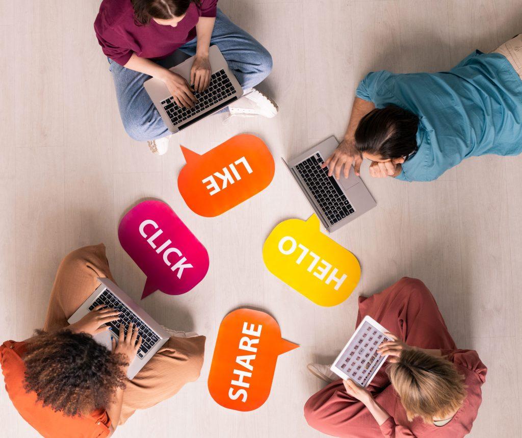 Un grupo de personas trabajan en ordenadores sentados en el suelo.